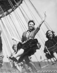 1953. Grande Bretagne. Leslie Caron sur un manège de fête foraine (Keystone) - Muzeo.com