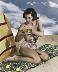 Jeune femme en bikini utlisant de la creme solaire sur une plage (anonyme) - Muzeo.com