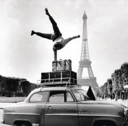UN GLOBE-TROTTER ACROBATE DEVANT LA TOUR EIFFEL 1956 (Keystone) - Muzeo.com