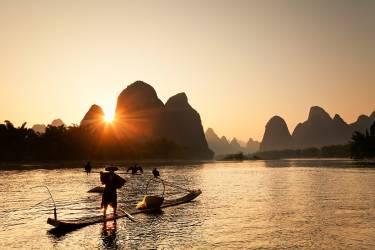 Chine, Guangxi Zhuangzu Zizhiqu, Yangshuo, pêcheur de cormorant sur la rivière Li au coucher du soleil, les montagnes karstiques en arrière-plan (Luigi Vaccarella) - Muzeo.com