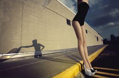 Femme en maillot de bain une pièce et chaussures à talons hauts debout contre une bordure de trottoir (Anonyme) - Muzeo.com