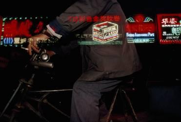 Homme à vélo passant les néons de la rue (Paul Chesley) - Muzeo.com