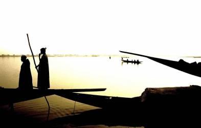 IN*Mali, Mopti, pirogues sur le fleuve Niger, silhouettes de deux piroguiers (Foubert Bernard) - Muzeo.com
