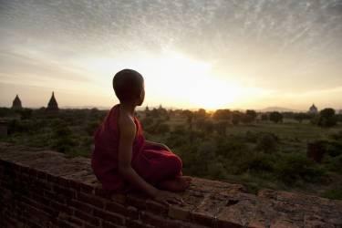 Jeune moine bouddhiste regardant le coucher du soleil (Scott Stulberg) - Muzeo.com