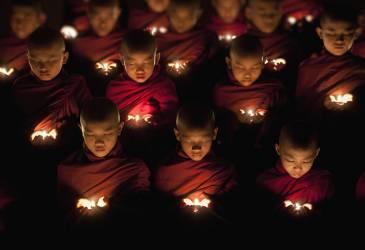 Jeunes moines bouddhistes priant à la lueur d'une bougie (Scott Stulberg) - Muzeo.com