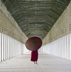 Moine bouddhiste marchant à travers le couloir d'un temple à Myanmar (Puddy Martin) - Muzeo.com