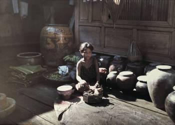 A Siamese girl sits on the floor beside glazed water jugs, Bangkok, Thailand, 1934 - produit fini (Courtellemont, Gervais) - Muzeo.com