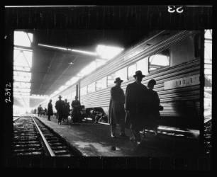 Hommes, probablement navetteurs, marchant le long du quai à côté d'un train (Stanley Kubrick) - Muzeo.com