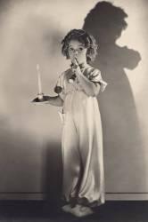 L'actrice americaine enfant Shirley Temple (nee en 1928) en chemise de nuit portant une bougie et posant le doigt sur sa bouche (silence chut) 1936 (Umberto anonyme) - Muzeo.com