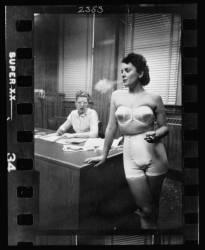 Modèle féminin, debout dans un bureau, fumant durant la confection de sous-vêtements (Kubrick Stanley) - Muzeo.com