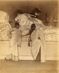 Deux étudiants en costume grec devant une copie en plâtre des