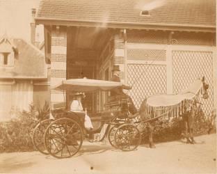Jeune femme assise dans une voiture à cheval devant une maison (anonyme) - Muzeo.com