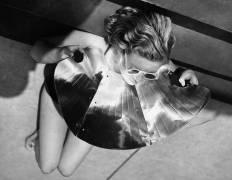 Jeune femme bronzant avec un réflecteur (Anonyme) - Muzeo.com